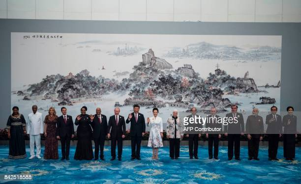 Chinese President Xi Jinping and his wife Peng Liyuan pose with BRICS leaders and other invited heads of state and their spouses for a family photo...