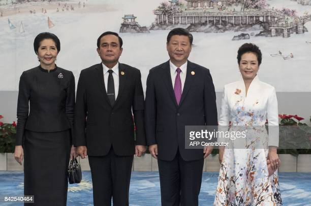 Chinese President Xi Jinping and his wife Peng Liyuan pose with Thai Prime Minister Prayut ChanOCha and his wife Naraporn during a photo opportunity...