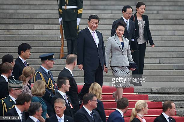 Chinese President Xi Jinping and his wife Peng liyuan wait for the arrival of Queen Margrethe II of Denmark during a welcome ceremony outside the...