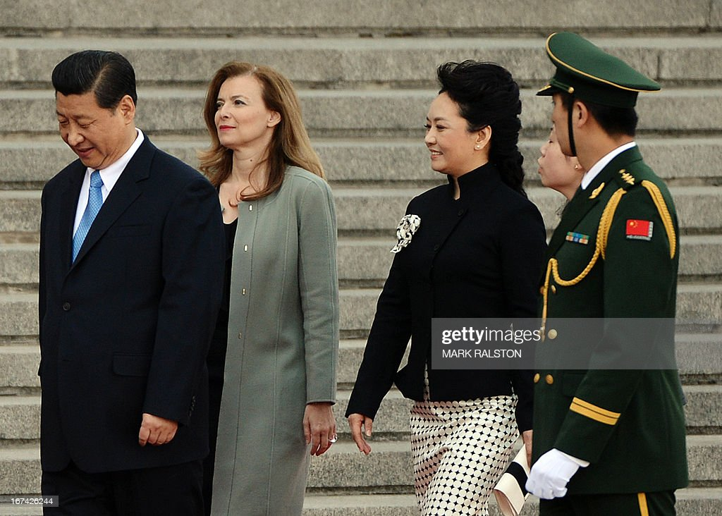 Chinese President Xi Jinping (L) and his wife Peng Liyuan (2nd R) with walk with the partner of the French president, Valerie Trierweiler (2nd L), as they prepare to review an honour guard outside the Great Hall of the People in Beijing on April 25, 2013. French President Francois Hollande, accompanied by a high-powered business delegation, started a two-day visit to China, with trade rather than geopolitics at the top of the agenda. AFP PHOTO/POOL/Mark RALSTON