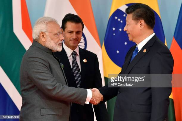 Chinese President Xi Jinping and Indian Prime Minister Narendra Modi shake hands before the group photo session at the Dialogue of Emerging Market...