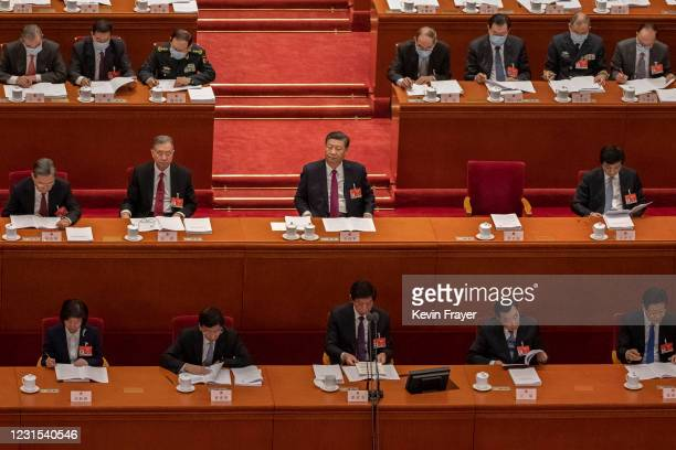 Chinese President Xi Jinping and lawmakers listen to Chinese Premier Li Keqiang speak at the opening session of the National People's Congress at the...