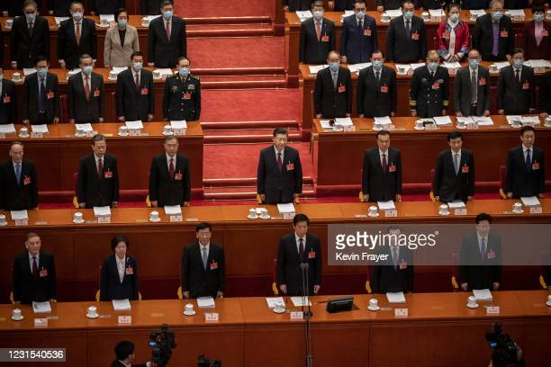 Chinese President Xi Jinping and members of the government stand during the national anthem at the opening session of the National People's Congress...