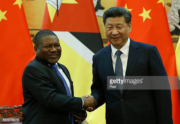 Chinese President Xi Jinping and Mozambican President Filipe Nyusi shake hands at a signing ceremony at the Great Hall of the People in Beijing China...