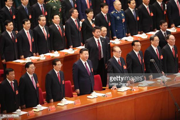Chinese President Xi Jinping and other Chinese politicians and delegates listen to the national anthem duirng the opening session of the Chinese...