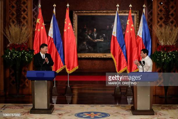 Chinese President Xi Jinping and Philippines' President Rodrigo Duterte react after a joint press statement at the Malacanang Presidential Palace in...