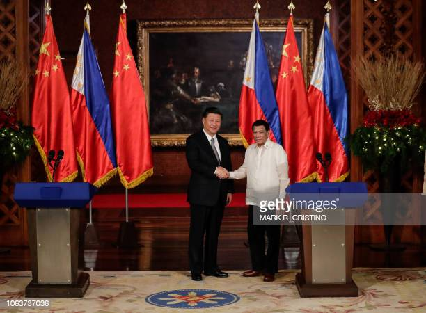 Chinese President Xi Jinping and Philippines' President Rodrigo Duterte shake hands after a joint press statement at the Malacanang Presidential...