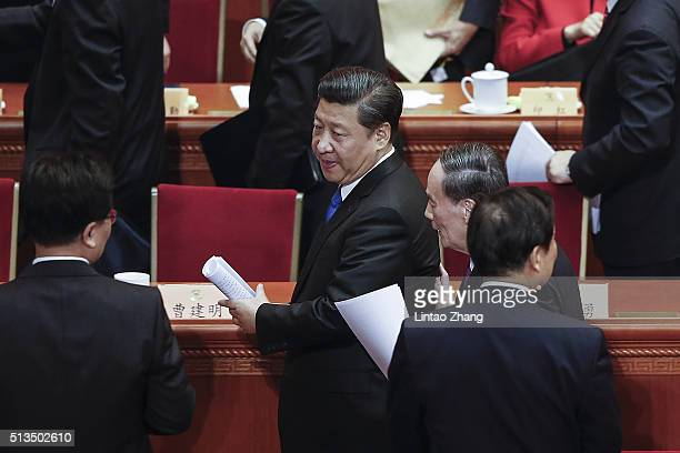 Chinese President Xi Jinping and Politiburo Standing Committee member Wang Qishan walk out together after the opening session of the Chinese People's...