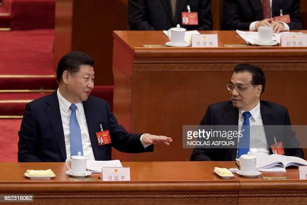 Chinese President Xi Jinping and Premier Li Keqiang attend the third plenary session of the fifth session of the 12th National People's Congress at...
