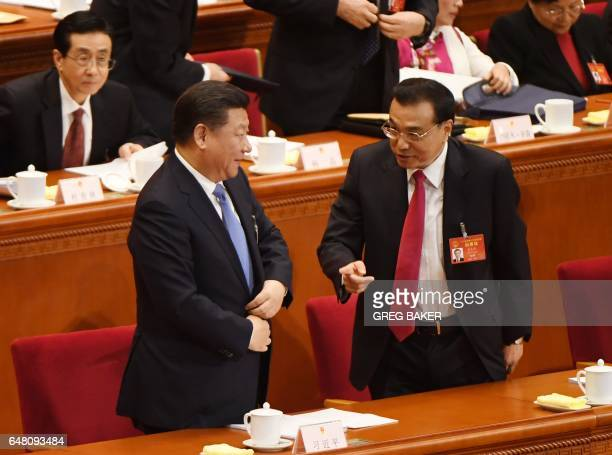 Chinese President Xi Jinping and Premier Li Keqiang chat at the end of the opening session of the National People's Congress, China's legislature, in...