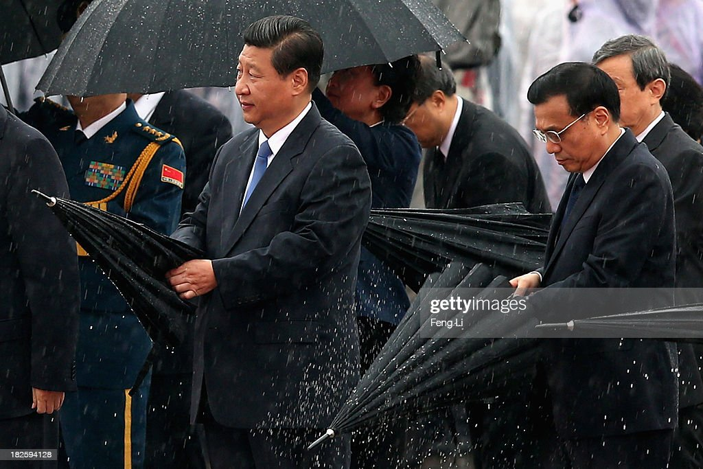 Chinese President Xi Jinping (Left) and Premier Li Keqiang (Right) close their umbrellas in the rain before bowing to the Monument to the People's Heroes during a ceremony marking the 64th anniversary of the founding of the People's Republic of China at Tiananmen Square on October 1, 2013 in Beijing, China. On October 1, 1949, Chinese leader Mao Zedong stood at the Tiananmen Rostrum to declare the founding of the People's Republic of China.