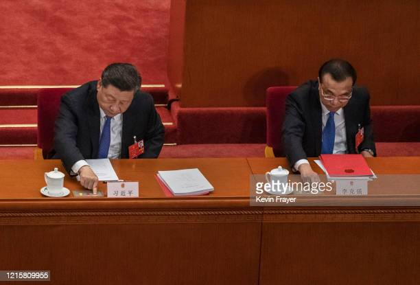 Chinese President Xi Jinping, and Premier Li Keqiang, right, press the green button as they vote on a new draft security bill for Hong Kong during...