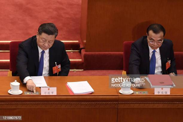 Chinese President Xi Jinping and Premier Li Keqiang vote on a proposal to draft a security law on Hong Kong during the closing session of the...
