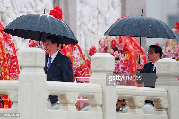 Chinese President Xi Jinping and Premier Li Keqiang walk past the Monument to the People's Heroes while holding umbrellas during a ceremony marking...