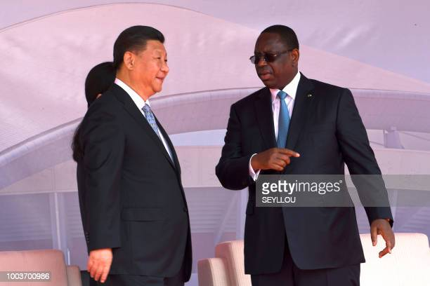 Chinese President Xi Jinping and Senegalese President Macky Sall speak as they arrive for the inauguration ceremony of a wrestling arena built by a...