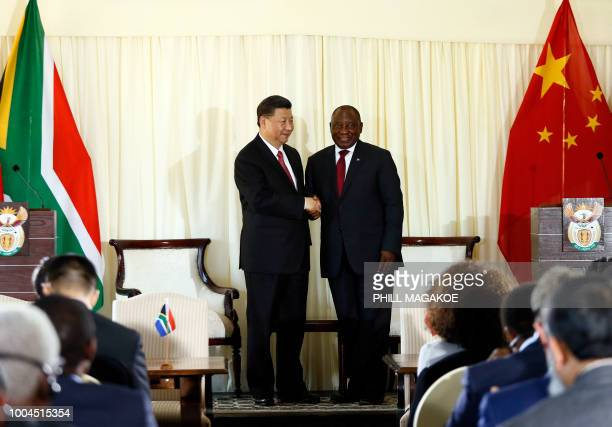 Chinese President Xi Jinping and South African President Cyril Ramaphosa shake hands after a press conference following their meeting at the Union...