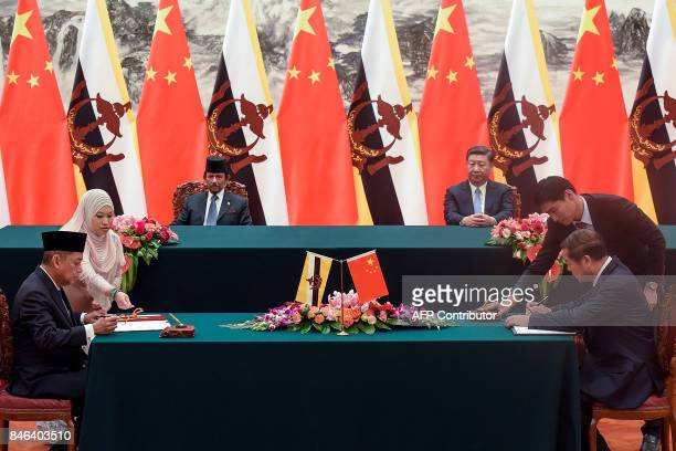 Chinese President Xi Jinping and Sultan of Brunei Hassanal Bolkiah attend a signing ceremony following their bilateral meeting while Chinese Minister...