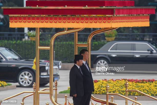Chinese President Xi Jinping and Sultan of Brunei Hassanal Bolkiah listen to their national anthem during a welcoming ceremony outside the Great Hall...