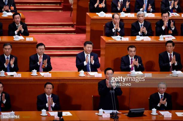 TOPSHOT Chinese President Xi Jinping applauds after the voting result is announced during the third plenary session of the first session of the 13th...