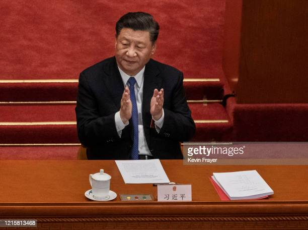 Chinese president Xi Jinping, applauds the results of a vote on a new draft security bill for Hong Kong during the closing session of the National...