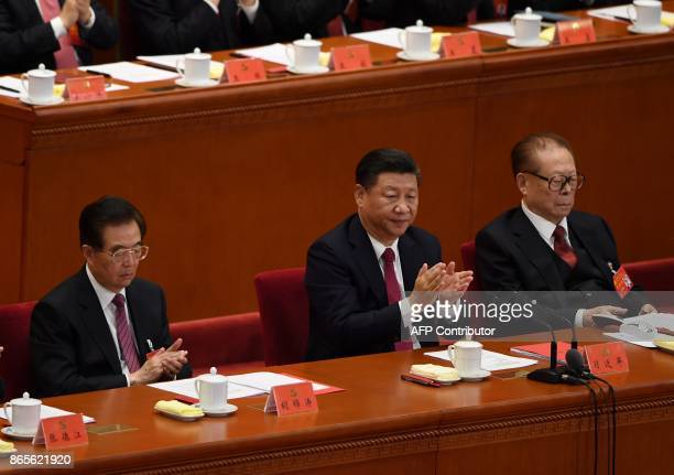 Chinese President Xi Jinping applauds with China's former presidents Jiang Zemin and Hu Jintao during the closing of the 19th Communist Party...