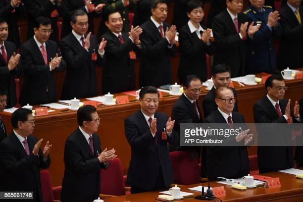 Chinese President Xi Jinping applauds with former presidents Hu Jintao and Jiang Zemin Premier Li Keqiang and National People's Congress Chairman...