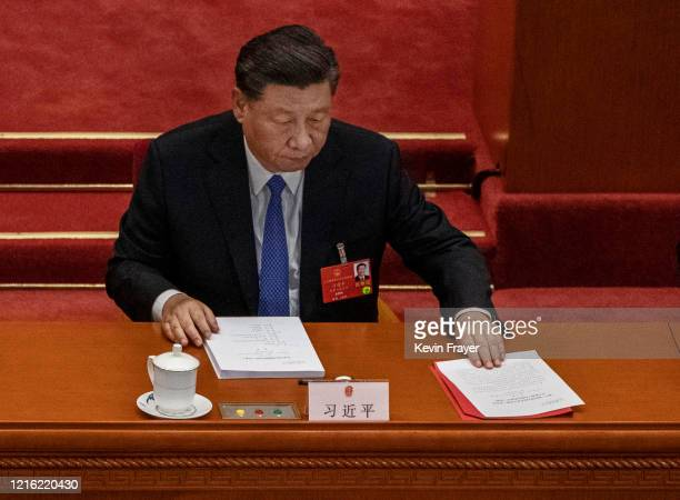 Chinese president Xi Jinping arranges his papers at the closing session of the National People's Congress, which included a vote on a new draft...