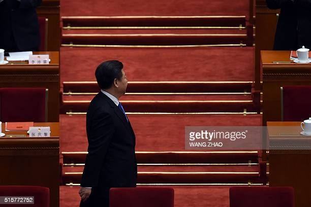 Chinese President Xi Jinping arrives for the closing session of the National People's Congress in the Great Hall of the People in Beijing on March 16...
