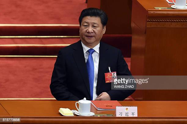 Chinese President Xi Jinping attends the closing session of the National People's Congress in the Great Hall of the People in Beijing on March 16...