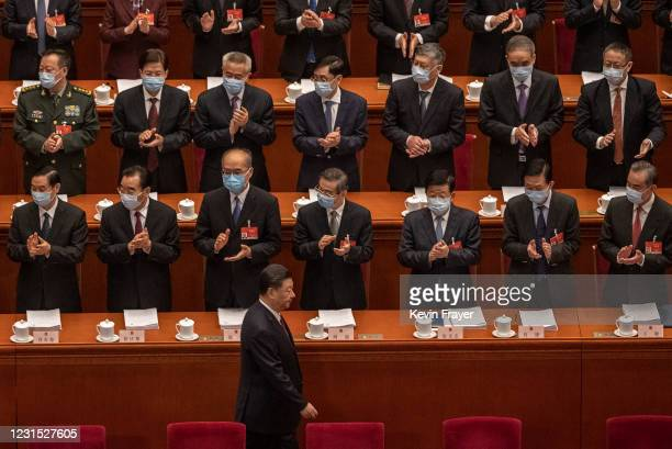 Chinese President Xi Jinping, bottom center, is applauded by members of the government as he arrives at the opening session of the National People's...
