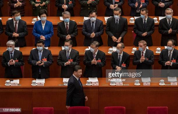 Chinese President Xi Jinping, bottom center, is applauded by members of the government as he arrives at the second plenary session of the National...