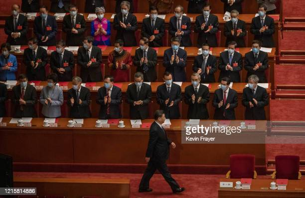 Chinese president Xi Jinping bottom is applauded by delegates as he arrives to the closing session of the National People's Congress which included a...
