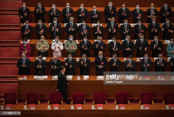 Chinese president Xi Jinping bottom is applauded by delegates wearing protective masks as he arrives to the closing session of the National People's...