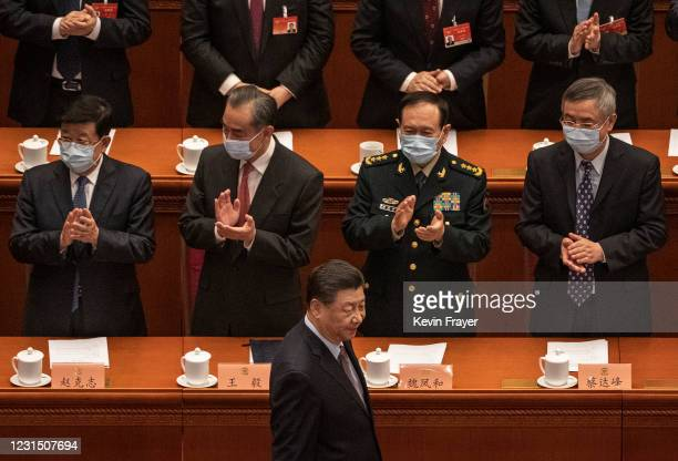 Chinese President Xi Jinping, bottom, is applauded by members of the government as he arrives to the opening session of the Chinese People's...