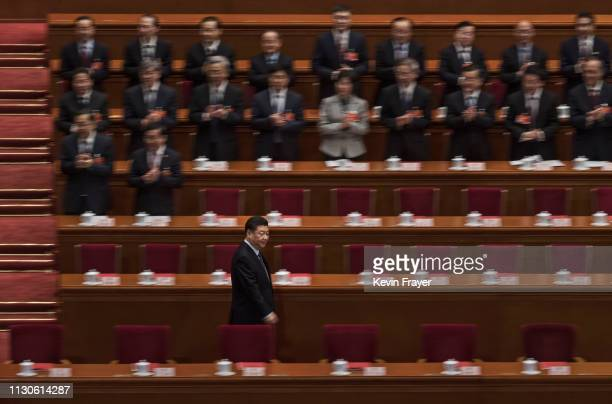 Chinese President Xi Jinping, bottom left, arrives for the closing meeting of the National People's Congress on March 15, 2019 in Beijing, China. The...
