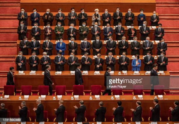 Chinese President Xi Jinping, bottom right, and Premier Li Keqiang, second right, Li Zhansu, third right, are applauded by members of the government...