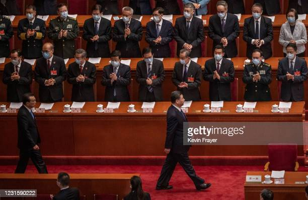 Chinese President Xi Jinping, bottom right, and Premier Li Keqiang, bottom left, are applauded by members of the government as they arrive at the...