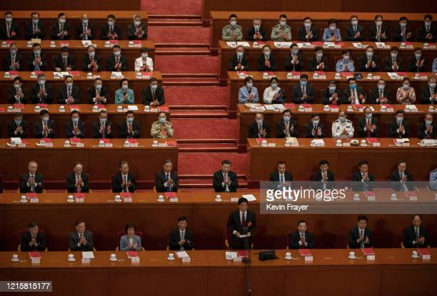 Chinese president Xi Jinping center and delegates applaud at the closing session of the National People's Congress which included a vote on a new...