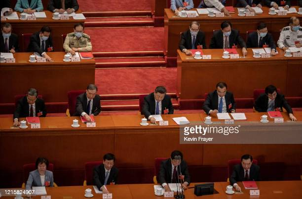 Chinese president Xi Jinping center and premier Li Keqiang center right and other members of the politburo and government vote on a new draft...