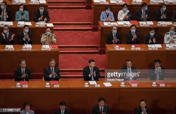 Chinese president Xi Jinping center and premier Li Keqiang center right and other members of the government applaud after the results of a vote on a...