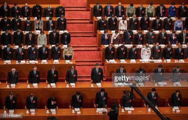 Chinese president Xi Jinping, center, and top members of government and delegates, many wearing masks, bow their heads as they observe one minute of...