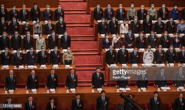 Chinese president Xi Jinping, center, and top members of government and delegates, many wearing masks stand during the national anthem at the opening...