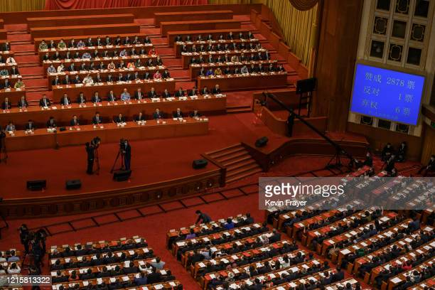 Chinese president Xi Jinping center left and Communist Party delegates look on as the results are announced after voting on a new draft security bill...