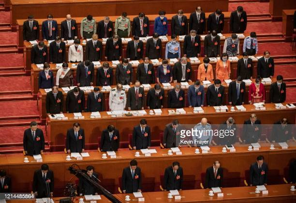 Chinese president Xi Jinping, center left, and top members of government and delegates, many wearing masks, bow their heads as they observe one...