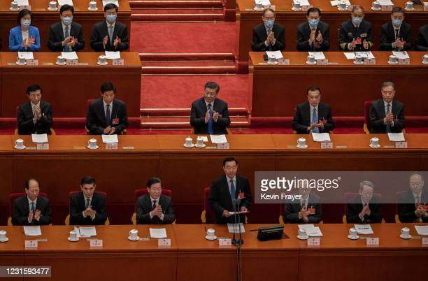 Chinese President Xi Jinping, center, Premier Li Keqiang, center second from right, and other lawmakers applaud during a speech by NPC Chairman Li...