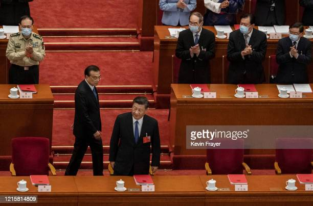 Chinese president Xi Jinping center right and premier Li Keqiangcenter left arrive to the closing session of the National People's Congress which...