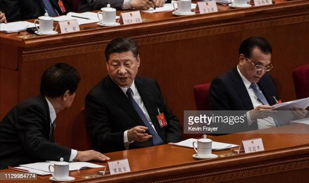 Chinese President Xi Jinping center speaks with Chairman of the National People's Congress Li Zhanshu as Priome Minister Li Keqiang right reads...