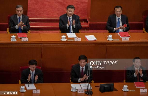 Chinese president Xi Jinping center top and premier Li Keqiang top right and other members of the government applaud after the results of a vote on a...