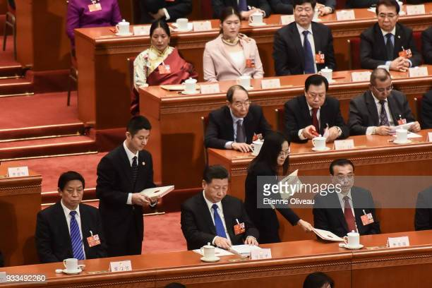 Chinese President Xi Jinping Chinese Premier Li Keqiang and Chairman of the National People's Congress Li Zhanshu receive they ballot from staff...