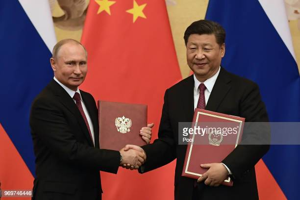 Chinese President Xi Jinping congratulates Russian President Vladimir Putin after presenting him with the Friendship Medal in the Great Hall of the...